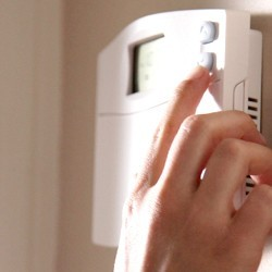 Hand reaching out to thermostat.