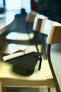 A scholar cap with a diploma on top of the cap, sitting on a chair.