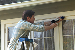 A man sealing a window to save on energy costs.