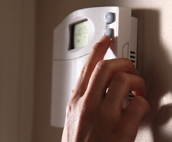 Adjusting the thermostat temperature to save energy costs.